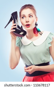 Young amazed woman using a shoe like a telephone holding it near her face and talking, blue background. Pin-up style.