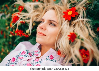 Young amazing beautiful blond girl in embroidered dress with pattern lifestyle portrait. Country fashion. Stylish happy cheerful female in traditional folk clothes lying and relaxing in flower bed.
