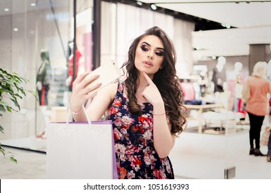 Young amazing woman make photo with mobile phone, shopping day on black friday, amazing woman with natural beauty, curl brunette hair