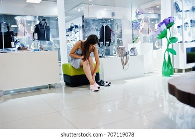 Young amazing woman trying on sport shoes in the shop while sitting.