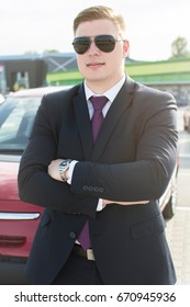 Young ambitious businessman hand crossed looking at the camera while standing in front of his car. Suit and tie businessman in front of a modern office building.