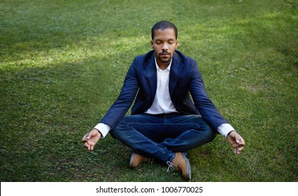 Young american african businessman in informal clothes meditating in lotus pose taking a deep breath at green grass.Business yoga and stress free environment.Peace of mind concept.Blurred
