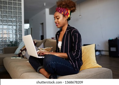 Young american african female blogger working remotely on digital netbook with internet text. African woman copywriter typing article for website on keyboard of modern laptop computer at home.