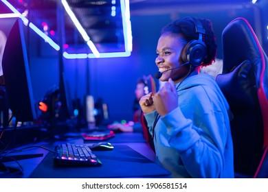 Junge amerikanische Lächelin-Profi-Gamer gewinnen im Online-Videospiel mit Kopfhörern, neonem Hintergrund.