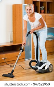 Young american blonde in casual using domestic hoover during clean-up