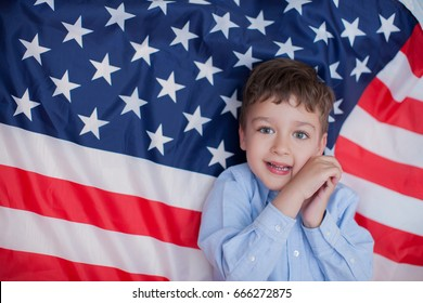 Young American boy and  flag at 4th July. Patriotic holiday. Fourth of July Independence Day in the United States.