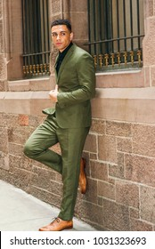 Young American Businessman Street Fashion in New York, wearing green suit, black undershirt, brown leather shoes, standing against vintage wall with windows, looking away, taking work break, thinking.