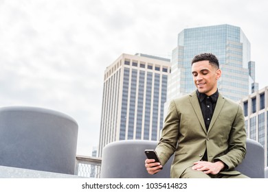 Young American Businessman traveling in New York, wearing green suit, siting at street park in business district with high building, texting on cell phone, smiling.