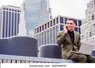 Young American Businessman traveling, working in New York, wearing green suit, siting at street park in business district with high building, working on laptop computer, talking on cell phone.