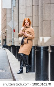 Young American businesswoman texting on cell phone, traveling in New York, wearing long brown woolen overcoat, long black leather boots, sitting on metal pillar on street, taking work break.