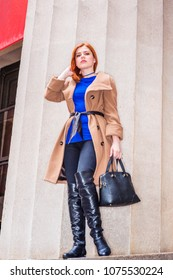 Young American businesswoman traveling, working in New York, wearing long brown woolen overcoat, blue undershirt, black pants, long leather boots, holding hand bag, standing by column, looking.