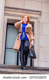 Young American businesswoman traveling, working in New York, wearing long brown woolen overcoat, blue undershirt, black pants, long leather boots, holding hand bag, walking down stairs, smiling.