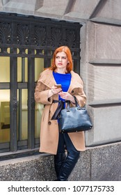 Young American businesswoman traveling, working in New York, wearing long brown woolen overcoat, blue undershirt, carrying  bag, standing by vintage window on street, texting on cell phone, thinking.