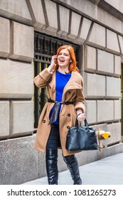 Young American businesswoman traveling, working in New York, wearing long brown woolen overcoat, blue undershirt, long leather boots, carrying bag, walking on vintage street, calling on cell phone.