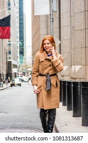 Young American businesswoman traveling, working in New York, wearing long brown woolen overcoat, black leather boots, talking on cell phone, walking on narrow vintage street in cold winter day.