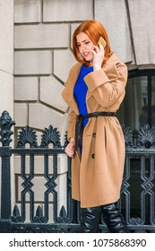 Young American businesswoman, wearing long brown woolen overcoat, blue undershirt, standing by metal railing outside office building, looking down, talking on cell phone, thinking.