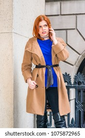 Young American businesswoman, wearing long brown woolen overcoat, blue undershirt, standing by metal railing outside office building, looking down, talking on cell phone, frowned, thinking.