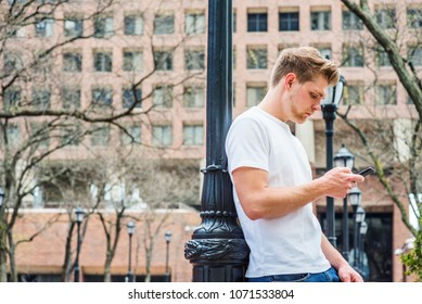 Young American College Student with little beard, looking down, reading, texting on cell phone in New York, wearing white T shirt, standing against light pole on campus, Modern daily life.