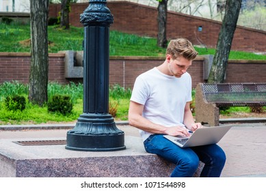 Young American College Student with little beard studying, working in New York, wearing white T shirt, blue jeans, sitting by light pole outdoor on campus, looking down, working on laptop computer.