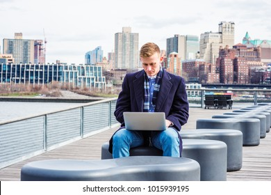 Young American College Student traveling, studying in New York, wearing blue long woolen overcoat, scarf, jeans, sitting by East River, working on laptop computer. Brooklyn buildings on background