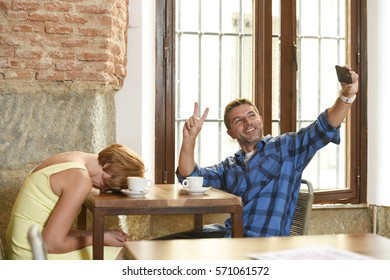 young American couple at coffee shop with mobile phone addict man taking selfie photo ignoring bored sad and frustrated woman girlfriend or wife in relationship problem and addiction concept