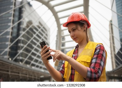 Young American female engineer with orange helmet using smartphone or mobile phone to check construction project plan ordered by construction site manager in Bangkok city. Industrial concept