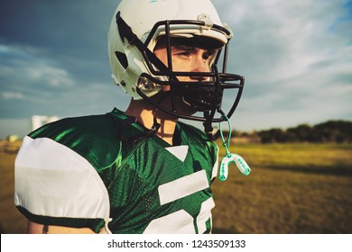 Young American football player taking a break with his mouth guard hanging from his helmet during a team practice session