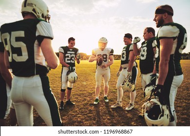 Young American football quarterback discussing offensive plays with his teammates during a practice session outside on a sports field in the afternoon