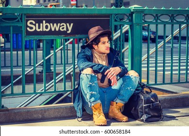 Young American Man with freckle face, curly hair, traveling in New York,  wearing blue jacket, jeans, yellow boot shoes, Fedora hat, black leather bag on ground, sitting on street by Subway sign.