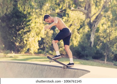 young American man in naked torso practicing radical skate board jumping and enjoying tricks and stunts in concrete half pipe skating track in sport and healthy lifestyle concept