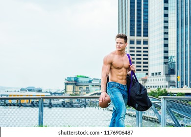 Young American Man, shirtless, half naked, showing strong, sexy body, waring jeans, carrying big duffel bag, holding American football, walking from business district, going to play field after work.
