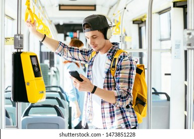 Young american man students is standing in a bus with smartphone, yellow backpack, headset on his head and listening to the music. People travel transport concept.