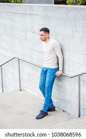 Young American Man wearing light gray collarless, knit pullover sweater, blue jeans, black sneakers, standing by wall in New York in spring day, sad, thinking, lost in thought.