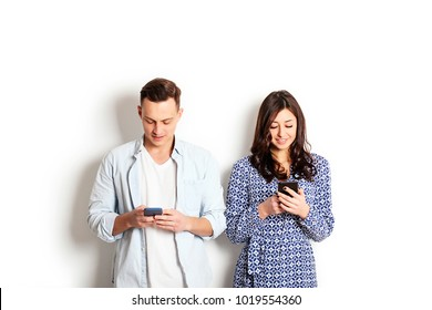 Young american man & woman holding staring at mobile cell phone. Male & female model blue jeans plaid shirt dress. Nomofobia concept. Smartp hone zombie, addiction disorder, iad. Copy space background