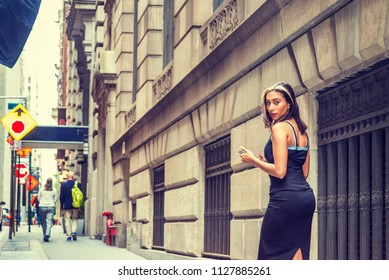 Young American Woman with black hair, dyed front top little blonde, wearing black sleeveless open back dress, walking on street by vintage wall with windows in New York, texting, turning back, looking