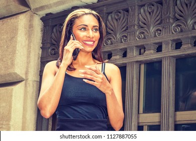 Young American Woman with black hair, dyed front top little blonde, wearing black sleeveless slim fit dress, standing by old style windows on street in New York, talking on cell pone, smiling.