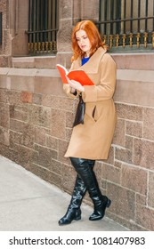 Young American Woman reading red book outdoor in New York, wearing long brown woolen overcoat, long black leather boots, standing against vintage wall with windows on street in winter day.