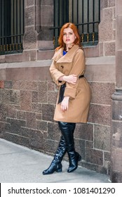 Young American Woman traveling in New York, wearing long brown woolen overcoat, black leather boots, hand touching arm, stranding against vintage wall with window, relaxing, thinking.