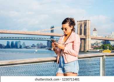 Young American Woman traveling in New York, wearing pink leather jacket, blue Denim shorts, sunglasses, standing by East River, texting on cell phone. Brooklyn, Manhattan bridges, boats on background.