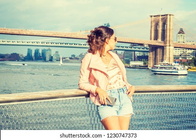 Young American Woman traveling in New York, wearing pink leather jacket, blue ripped Denim shorts, sunglasses, standing by river, looking back. Brooklyn, Manhattan bridges, boats on background.