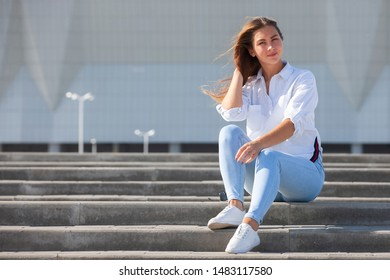Young American woman in a white T-shirt in jeans in white trendy sneakers relaxes sitting on the steps. Cute european girl model enjoys the rest. Spring style women's clothing. Portrait.