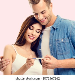 Young amorous happy couple, finding out results of a pregnancy test, over pink background. Caucasian models - in love, relationship, dating, happy lovers, family concept.