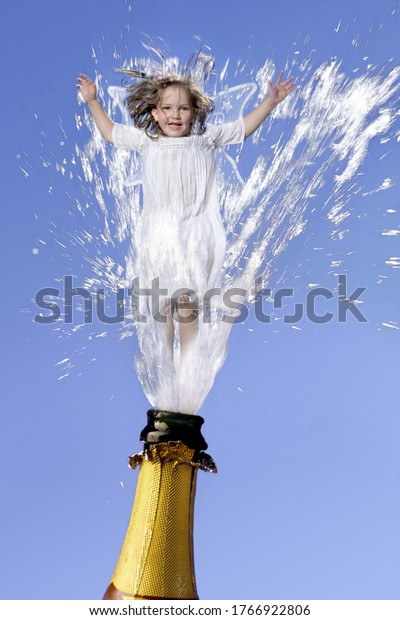 Young angel girl shooting out of champagne bottle