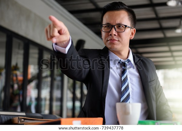 Young angry Businessman boss manager in office point his finger to complaint for project work delay and unsuccessful. Business concept for failure or disappointing.