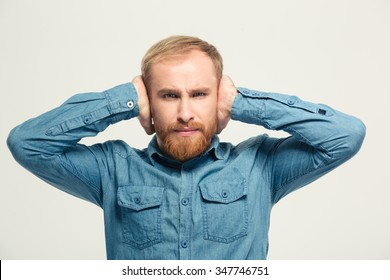 Young angry frustrated handsome bearded man closed ears by hands over white background