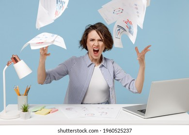 Young angry indignant sad director employee business woman in casual shirt sit work at white office desk with pc laptop throwing up paper account documents isolated on pastel blue background studio