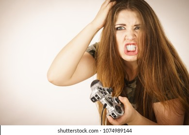 Young angry mad woman playing on the video console holding game pad. Gaming gamers concept.