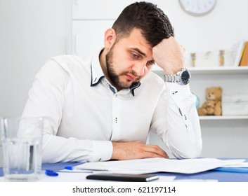 Young angry male worker having problem in project in office