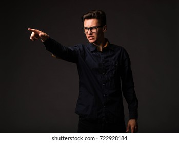 Young angry man portrait of a confident businessman showing by hands on a black background. Ideal for banners, registration forms, presentation, landings, presenting concept.