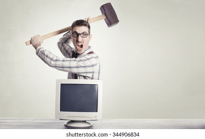 young angry nerd destroying old computer monitor